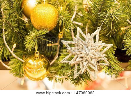 close up beautiful gold star and gold ball decorated on Chirstmas tree