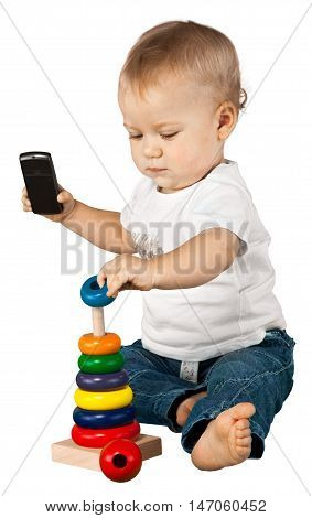 Baby boy holding a mobile phone and playing with a toy