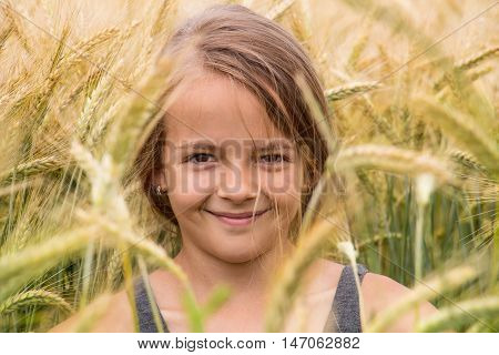 Summer portrait of a smiling young girl in the wheat field - closeup