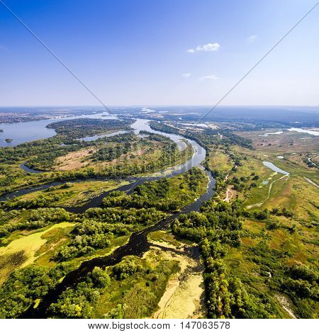 Summer landscape in rich colors from above. Aerial view. Outdoor. Lush green field with river and backwater skyline.
