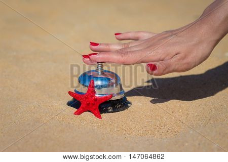Close up of female hand pressing service bell on sandy beach. Summer vacation concept.