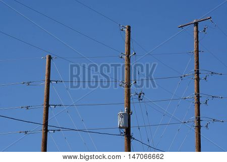 Electric power lines and poles against blue sky