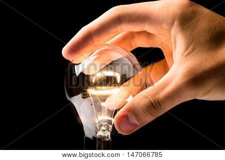 Hand Holding Standard Incandescent Light Bulb on Black Background