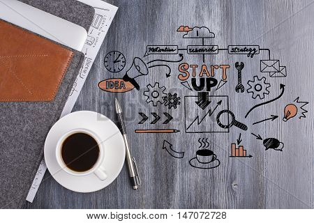 Top view of wooden desktop with business doodle coffee cup pen and electronic device in cover. Start up concept