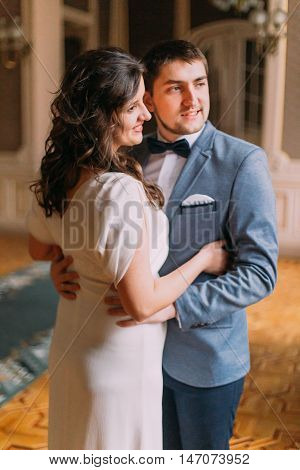 Beautiful newlywed pair have a sweet romantic moment in the luxurious vintage hall.