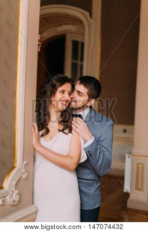 Charming newlywed pair embracing in vintage victorian mansion interior.