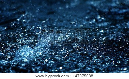 picture of a Water drops levitating in the air in dark. Splashing water fly in the air. Part of the drops is in focus part - out of the focus.Blue effect added