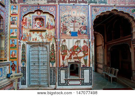 NAWALGARH, INDIA - FEB 6, 2015: Life of people on the murals in courtyard of old mansion called Haveli on February 6 2015. With population of 100000 Nawalgarh is the education center of Shekhawati region