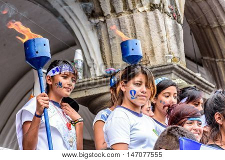Antigua Guatemala - September 14 2015: Girls with patriotic headbands & face stamps hold lit torches outside city hall during Guatemalan Independence Day celebrations