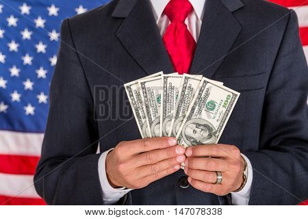 Businessman Showing Dollar Bills with American Flag on Background