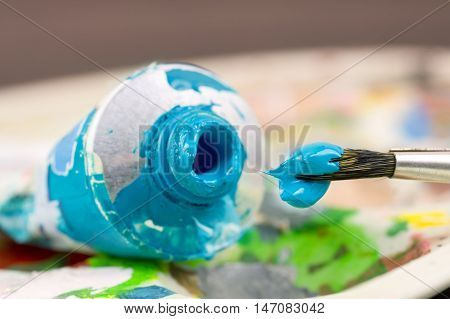 artistic paint brush with blue (turquoise) paint