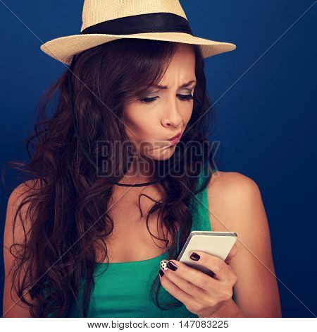 Grimacing Young Woman In Hat Looking On Mobile Phone With Question Sing On The Face. Toned Closeup P