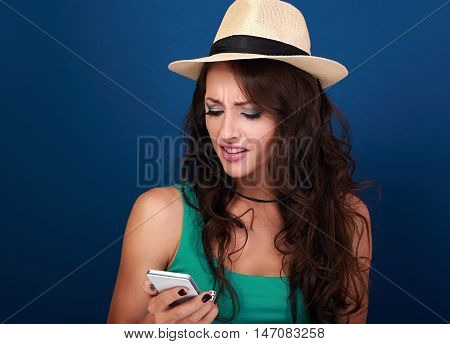 Unhappy Angry Woman In Hat Looking On Mobile Phone In Stress Emotion On Blue Background