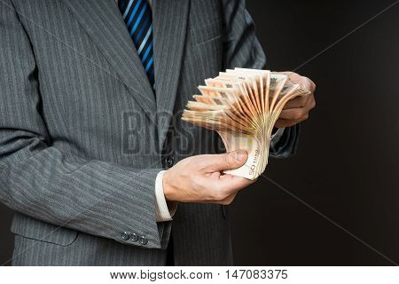 Business man is holding cash fan of fifty euros. Person counts money. Businessman hands and euro bills isolated gray background.