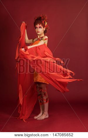 Phoenix woman. Flaming young girl on the red background