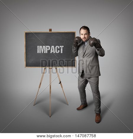 Impact text on  blackboard with businessman wearing boxing gloves