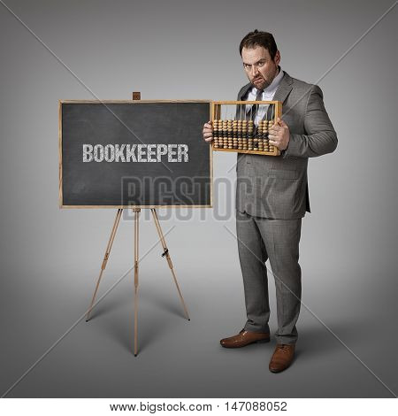 Bookkeeper text on blackboard with businessman and abacus