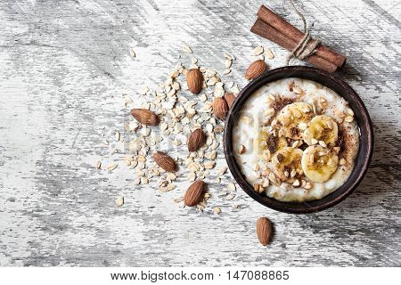 oatmeal porridge in ceramic bowl with banana almonds honey and cinnamon on white wooden background. healthy breakfast. top view