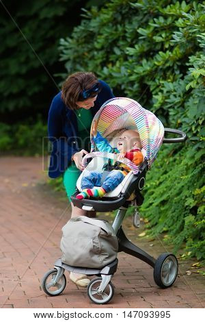 Young working mother and formal office outfit walking with her baby in colorful stroller. Mom and child in pushchair.