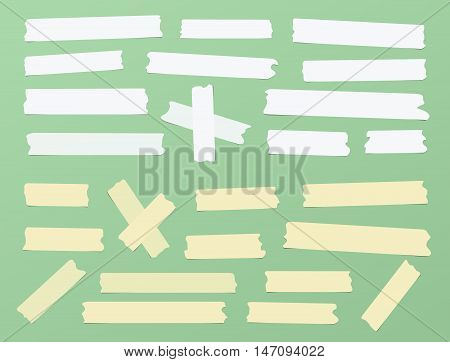 Pieces of different size, color, sticky, adhesive masking tape are on green background.