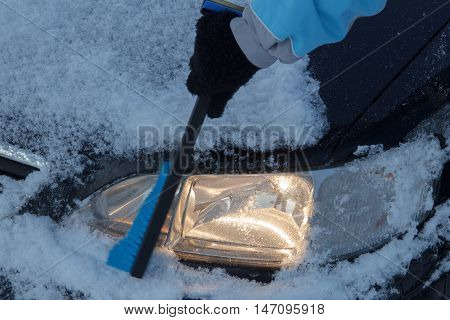 Snow covered car lights being cleared off