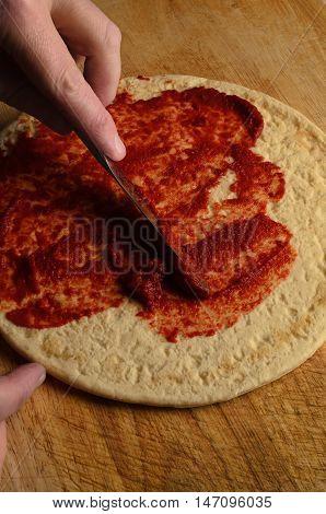 Hand Spreading Tomato Puree On Pizza Base