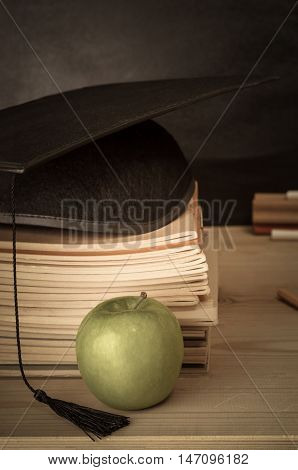 Education Concept. A wooden teacher's desk with stack of exercise books topped with mortarboard. Apple in the foreground. Blackboard duster and chalk in background. Faded hues for a vintage or retro effect.