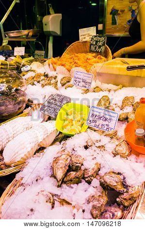 Countertop with various fresh seafood in Boqueria market. Barcelona. Shrimp, oysters, shells beautifully laid out in wicker baskets on the counter.