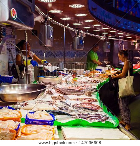 BARCELONA, SPAIN - AUGUST 25, 2016: A long counter with various fish and shellfish in Boqueria market. Barcelona. The process of buying a seafood.