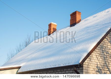 Two brick chimneys on a brick house with a snow covered roof