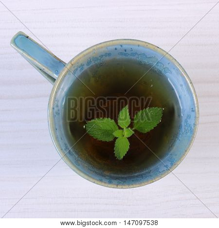 Lemon Balm In Cup Of Herbal Drink On White Wooden Table