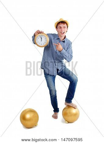guy points to the clock in the New Year's Eve. joyful guy with a clock in his hands the New Year night. clock at five minutes to midnight. the concept of New Year holiday. isolated on white background