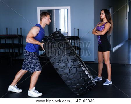 Young athletic man showing off - lifting a big tire the girl is looking at him