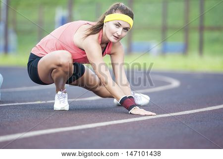 Young Caucasian Brunette Female in Athletic Sportgear Having Legs Stretching Excercises Outdoors. Horizontal Image Orientation
