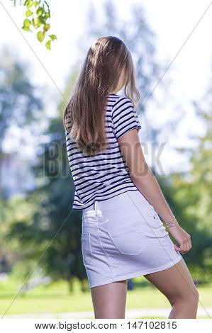 Teenager Lifestyle Concepts and Ideas.Back of Blond Caucasian Teenager Girl Outdoors. Vertical Image
