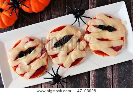 Halloween Mummy Mini Pizzas On White Plate Over Rustic Wooden Background