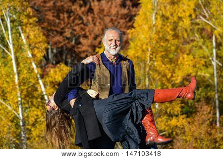 Happy vital elderly couple dancing and having fun in a bright sunny day on mountain meadow and birch forest in background
