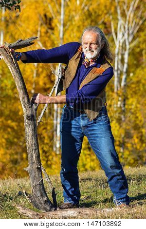 Strong vital elderly man dressed in hippie style in outdoor exercise using big heavy branches on mountain meadow in front of autumn birch forest