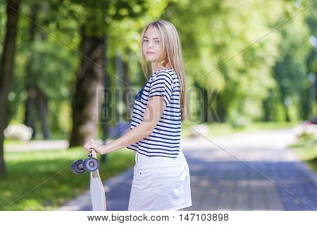 Teens Lifestyle Concepts and Ideas. Blond Caucasian Teenage Girl Posing With Long Skateboard in Green Forest. Horizontal Shot