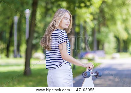 Teens Lifestyle Concepts and Ideas. Blond Caucasian Teenage Girl Posing With Long Skateboard in Green Forest Outdoors. Horizontal Image
