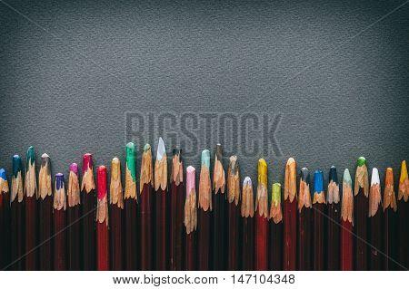 Row Of Artist Pastel Pencils On Gray Pastel Paper Sheet.