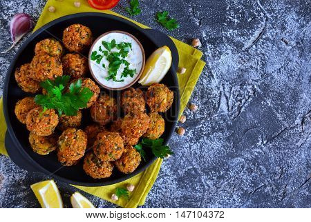 Falafel - deep fried balls of ground chickpeas with tahini sauce from