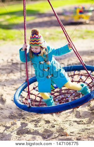 Little girl in warm coat and hat on a playground. Child playing outdoors in autumn. Kids play on school yard. Happy kid in kindergarten or preschool. Children having fun on cold fall day. Toddler on a swing.