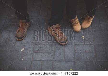Two pairs of legs in brown shoes on the background of gray paving slabs