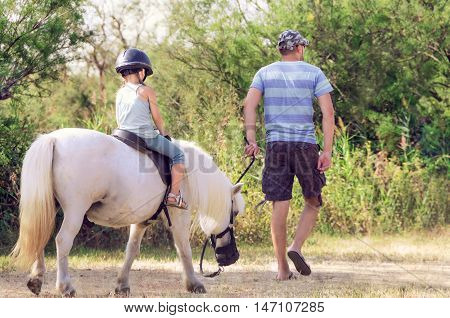 Dad teaches his daughter to ride a horse. Lesson with Riding Instructor.