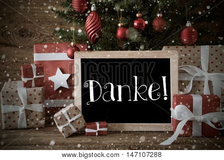 Nostalgic Christmas Card For Seasons Greetings. Christmas Tree With Balls And Snowflakes. Gifts In The Front Of Wooden Background. Chalkboard With German Text Danke Means Thank You