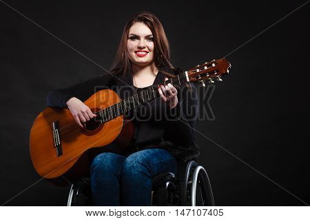 Real people disability and handicap concept. Teen girl handicapped guitarist sitting on wheelchair holds guitar studio shot on dark