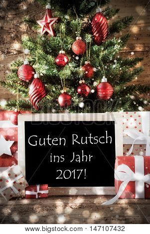 Christmas Tree With Balls And Snowflakes. Gifts Or Presents In The Front Of Wooden Background With Bokeh Effect. Chalkboard With German Text Guten Rutsch Ins Jahr 2017 Means New Year