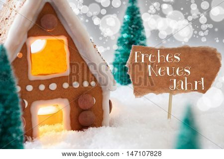 Gingerbread House In Snowy Scenery As Christmas Decoration. Trees And Candlelight For Romantic Atmosphere. Silver Background With Bokeh Effect. German Text Frohes Neues Jahr Means Happy New Year