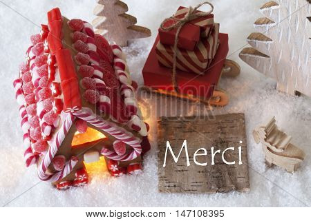 Label With French Text Merci Means Thank You. Gingerbread House On Snow With Christmas Decoration Like Trees And Moose. Sleigh With Christmas Gifts Or Presents.